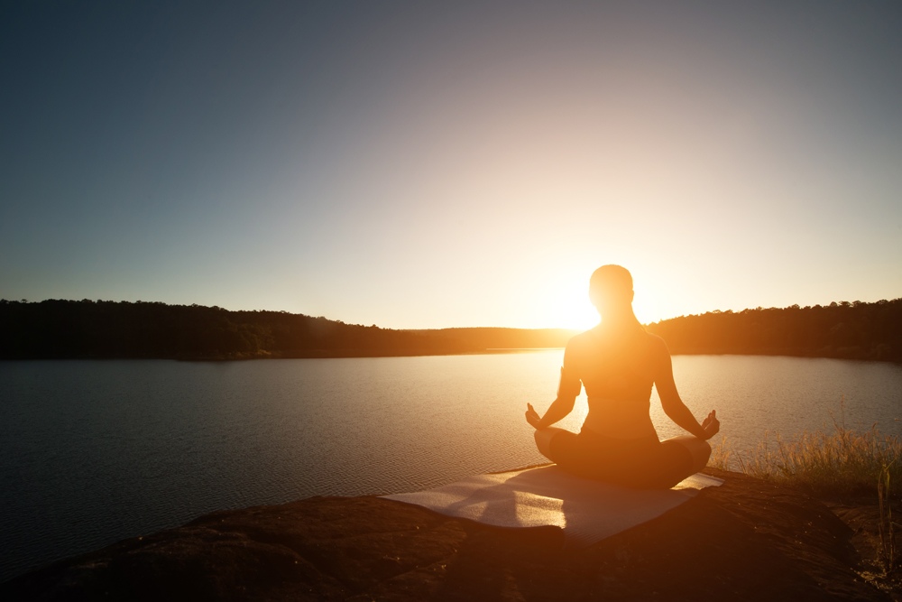 Silhouette of healthy woman is practicing yoga at mountain lake