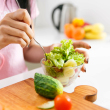 Close-up of woman's hands mixing salad in the kitchen